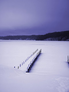 A pier and lake covered in snow.